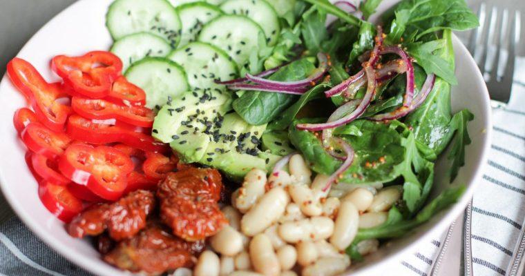Pupelių, paprikų, saulėje džiovintų pomidorų ir avokadų salotų dubuo su grūdėtųjų garstyčių padažu