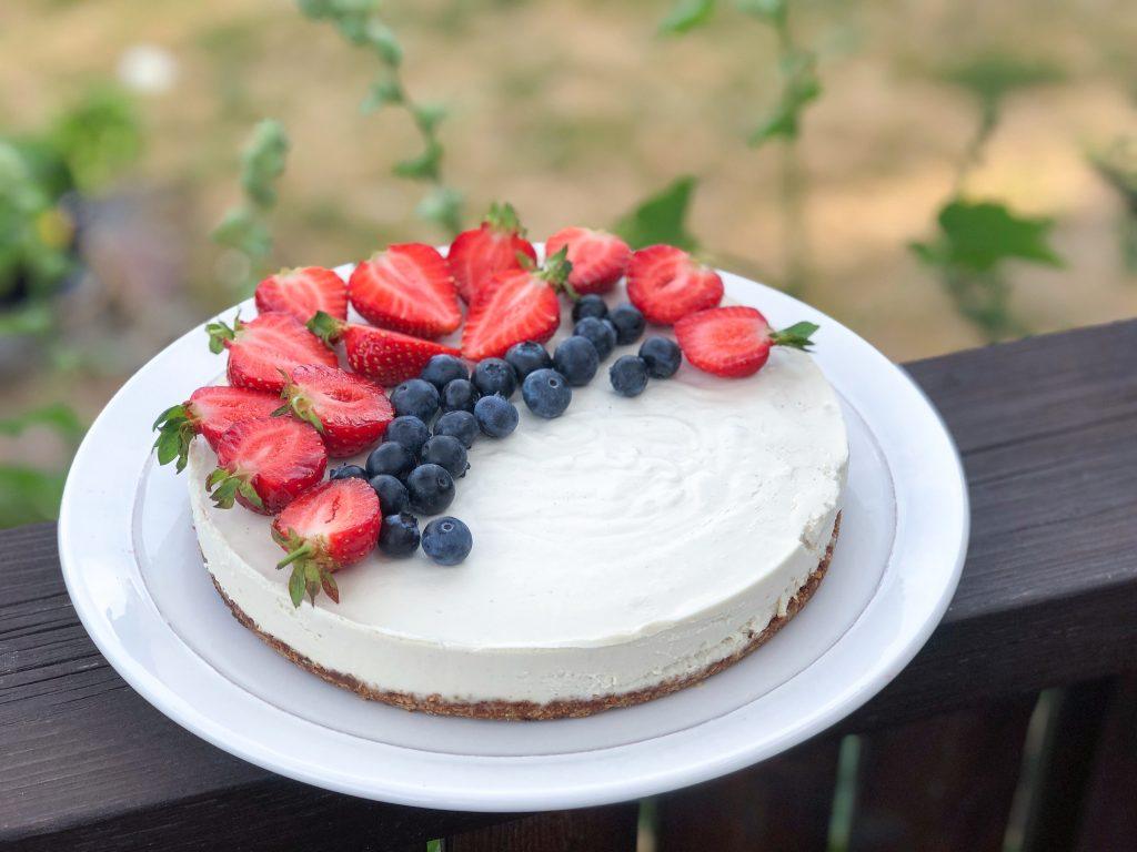 Veganiškas augalinis sūrio tortas, pagamintas iš anakardžių, kokoso pieno ir kakavos sviesto, papuoštas braškėmis ir šilauogėmis.