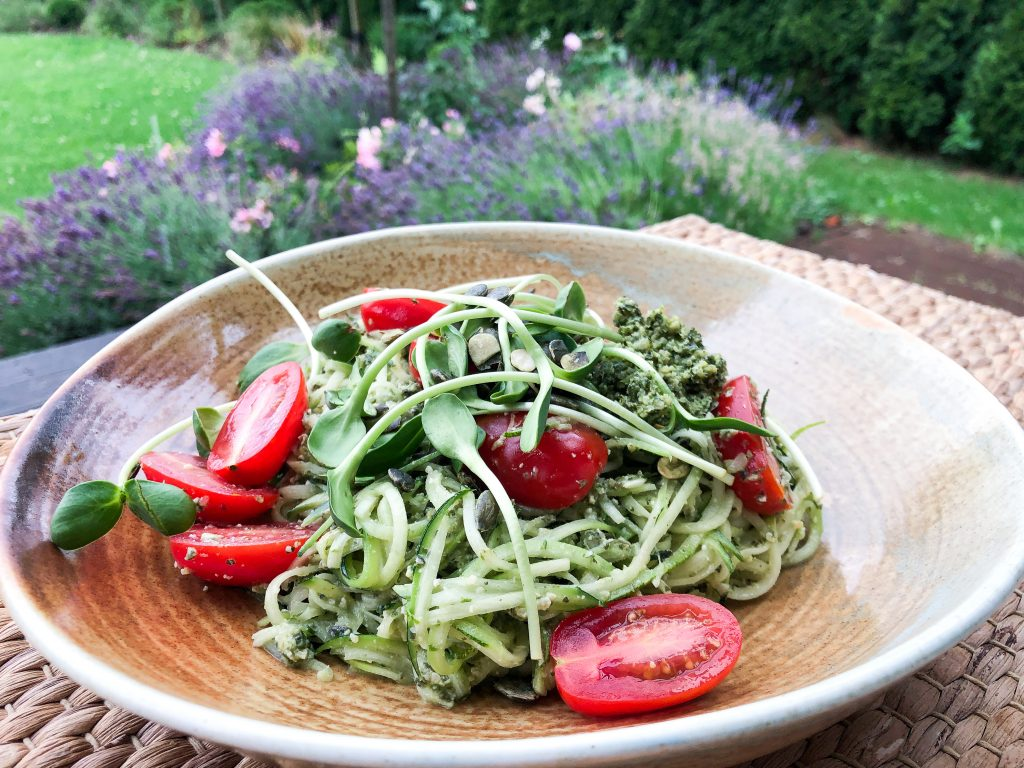 Šviežių cukinijų spagečių salotos su moliūgo sėklų pesto, šviežiais pomidorais ir saulėgrąžų daigais.